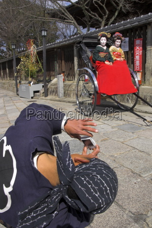 driver taking picture of two geishas