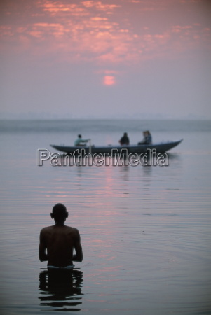 boat passing a man standing in