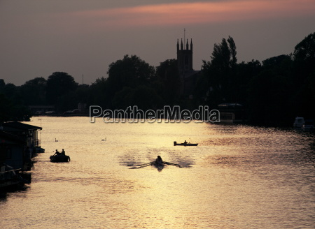 rowers on river thames with church