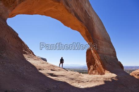 lone tourist hiker at wilson arch