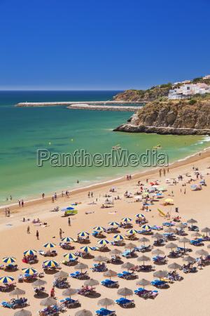 holidaymakers sunbathing under beach umbrellas on
