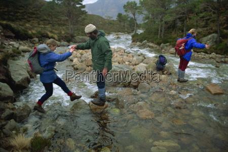 hikers crossing river in the ben