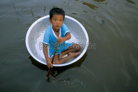 small boy in circular metal boat
