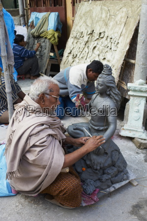 making clay statues of a hindu