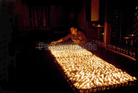 man lights butter lamps in the