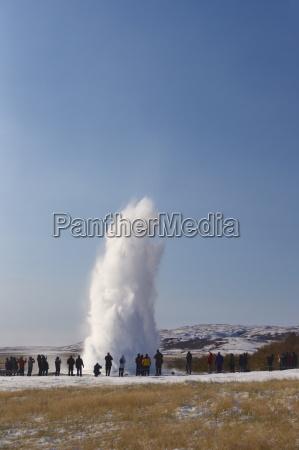 tourists watching geyser erupting strokkur the
