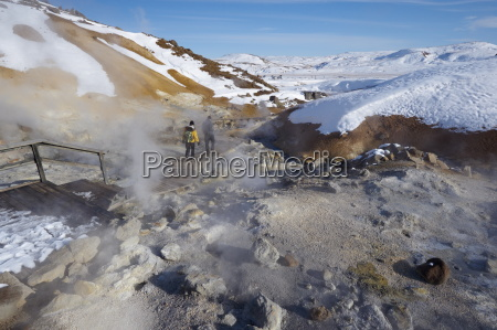 tourists watching geothermal activity of mudpots