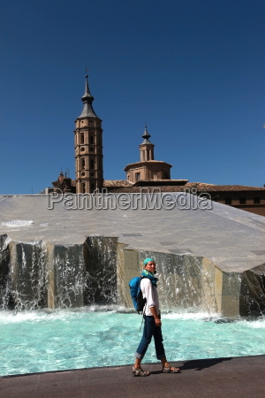 woman beside water features of plaza