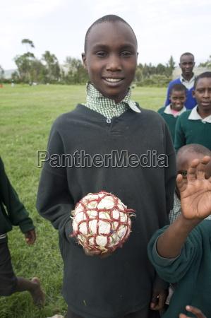 schoolboy in school uniform holding football