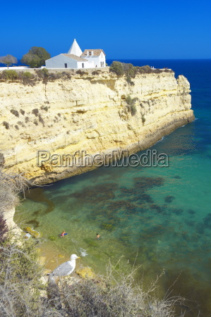 church on cliff by beach algarve