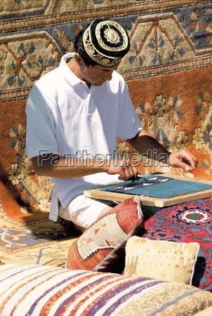 man weaving carpet marmaris anatolia turkey