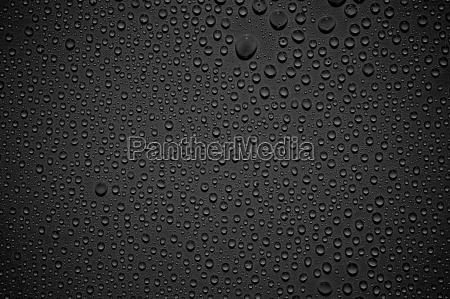 schwarzer hintergrund mit glaenzenden wassertropfen
