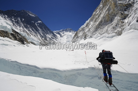 climbers crossing crevasse and ladder on