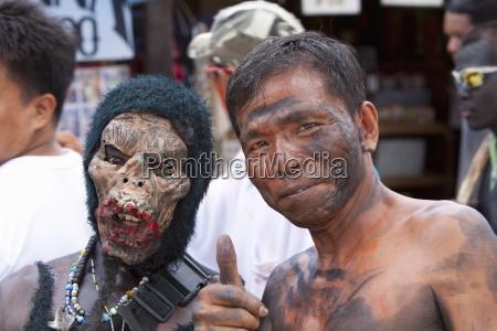 portraet zweier maenner einer maskiert der