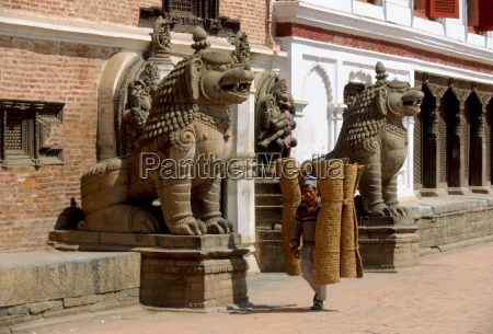 man carrying coir rugs through the