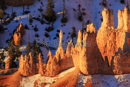 hoodoos and snow lit by strong