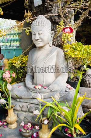 stone buddha statue covered in flowers