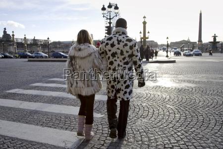pedestrians in winter coats walking across