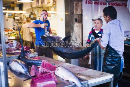 fischhaendler im begriff einen riesigen thunfisch