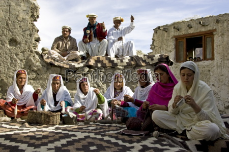 villagers spin wool and knit together