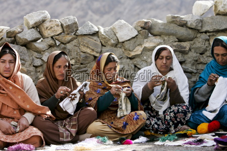 women sew together in mountain village