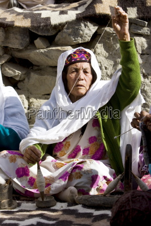 woman spins wool in mountain village
