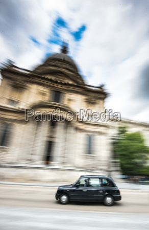 london taxi going past st pauls