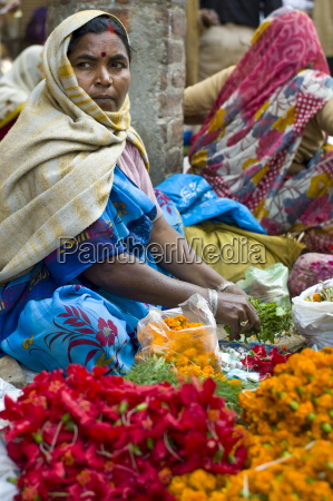 woman selling flowers and herbs for