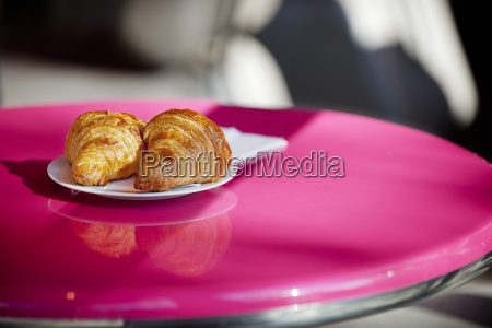 croissants on a pink cafe table