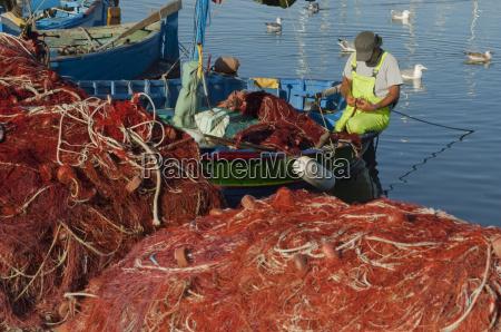 fisherman mending nets alghero sardinia europe