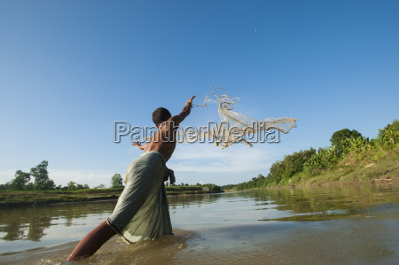 a man casts his net into