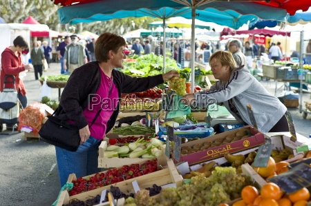 french woman buying grapes at fruit