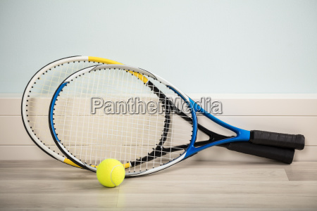 pair of rackets and a ball