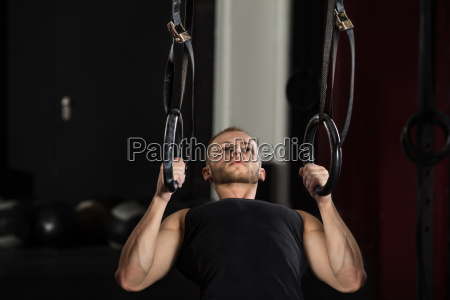 man exercising on gymnastic rings