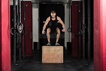 man doing a box jump exercise
