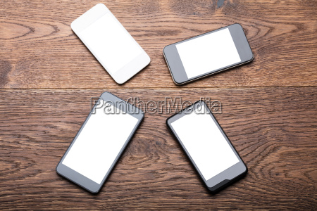 group of mobile phones on wooden