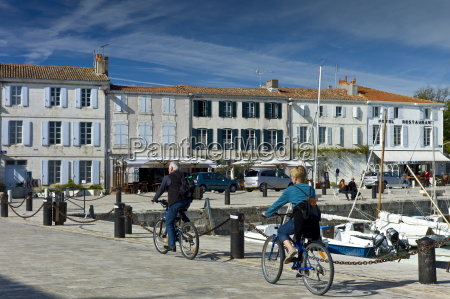 tourists cycling along the harbour at