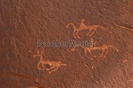 petroglyphs of riders on horseback hunting