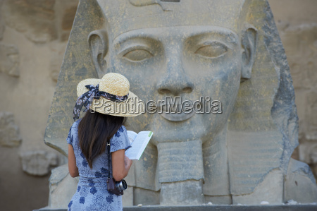 tourist studying a statue of the