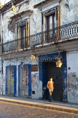 man walks along street with colonial