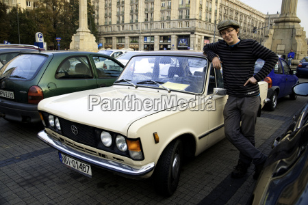 polish man stands beside his classic