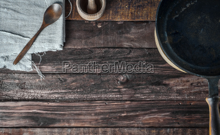 brown wooden background with black frying