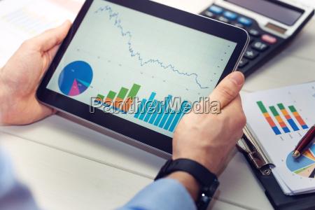 geschaeftsmann mit digitalen tablette mit diagrammen