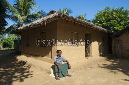 a man sitting outside his house