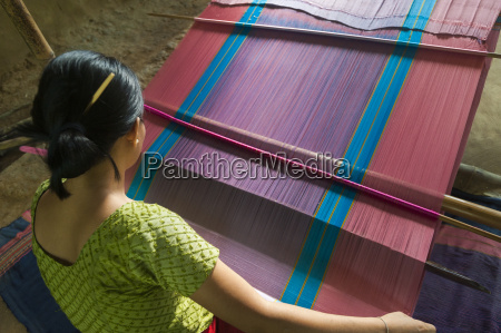 a woman weaves traditional clothes using