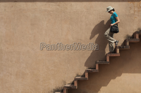 a tourist climbs downs some exposed