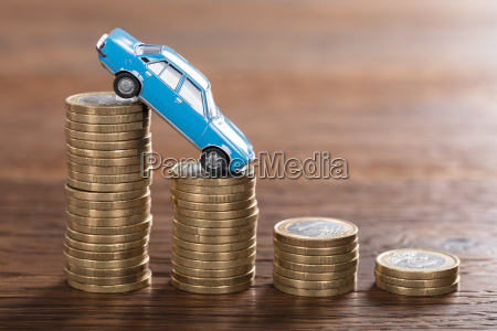 car model over a stacked coin