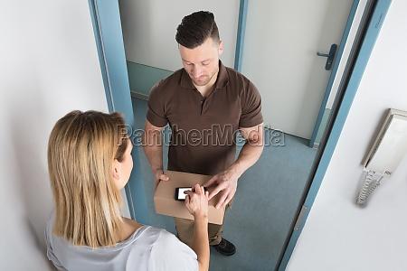 junge frau signing after receive lieferung