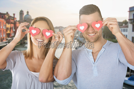 couple covering their eyes with paper