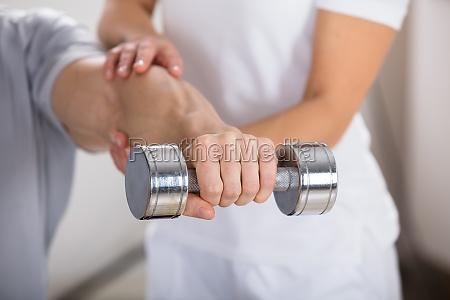 physiotherapeut hilft dem mann zu ueben
